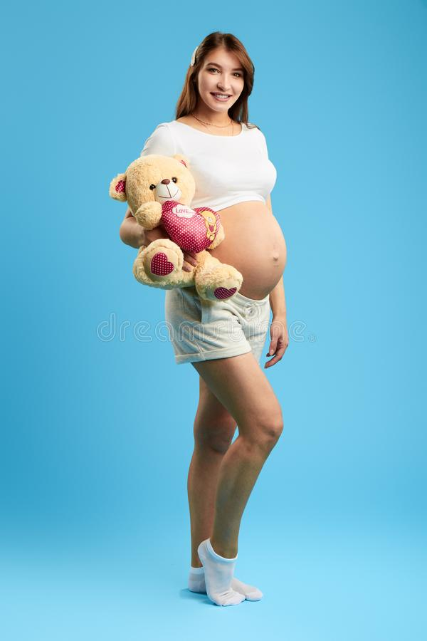 Charming beautiful pregnant woman holding a teddy bare and looking at the camera. Isolated blue background. studio shot. full length photo. happy pregnancy stock image