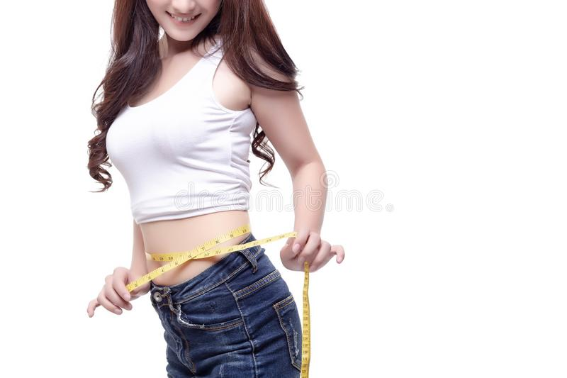 Charming beautiful woman gets satisfied of her body or figure. A. Ttractive beautiful girl can lose weight quickly. Pretty woman can wear favorite jeans again stock photography
