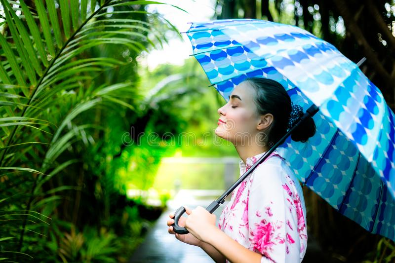 Charming beautiful woman hold a umbrella in rainy day at beautiful park. Gorgeous caucasian woman inhale fresh air. Lovely royalty free stock images