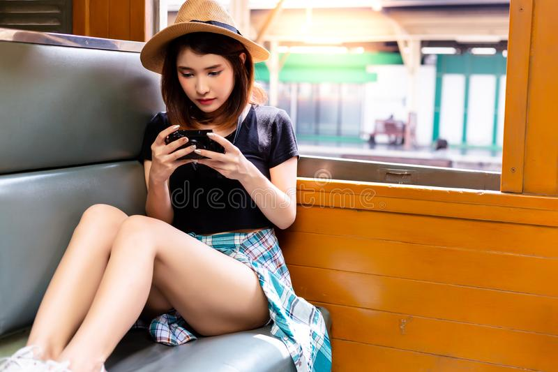 Charming beautiful woman is looking photos at camera during train is parking at a train station. Lovely girl sit on a vintage royalty free stock photography