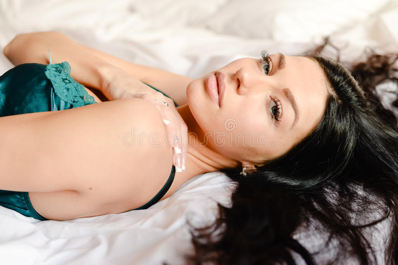 Charming beautiful woman in pretty turquoise silk shirt & looking at camera lying on the white bed background closeup portrait royalty free stock image