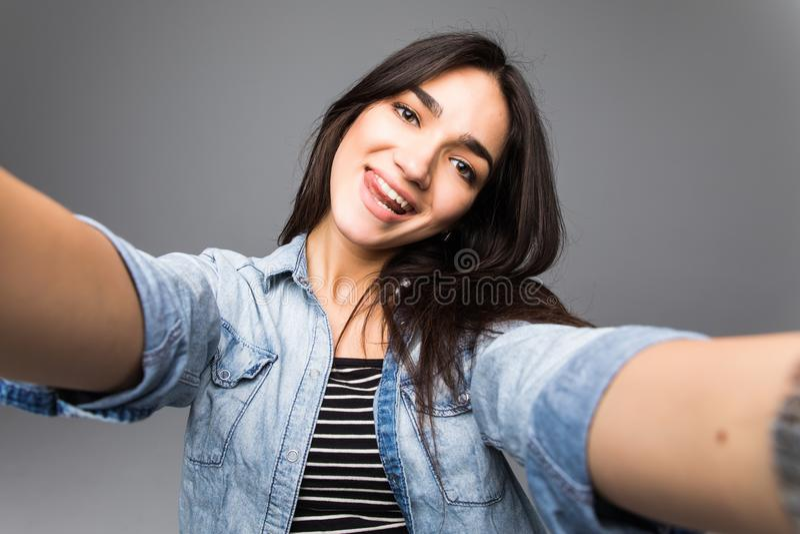 Charming young beautiful woman take selfie from hands on grey. Charming beautiful woman take selfie from hands on grey stock photo