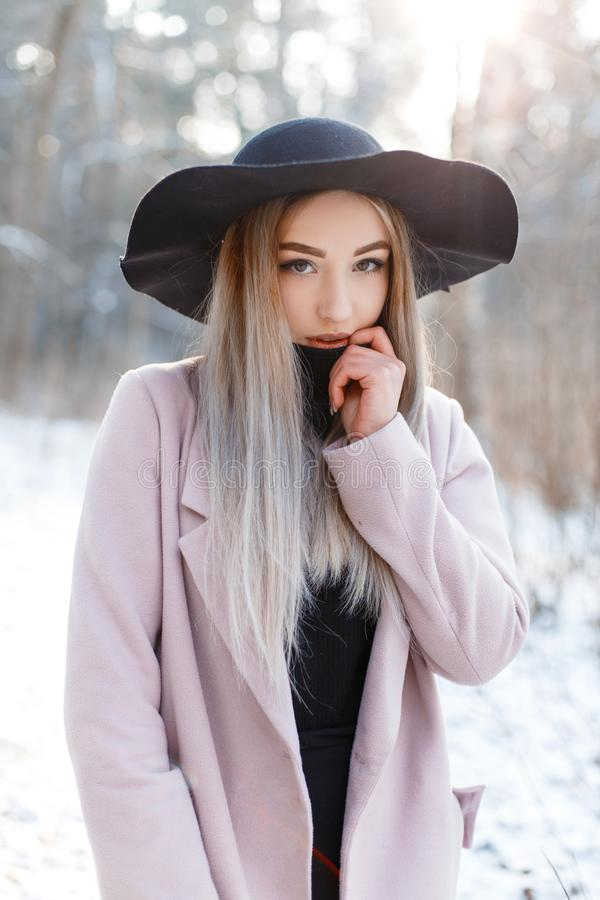 Charming beautiful young woman with blond hair in a knitted dress in a chic black hat in a pink elegant coat. Posing in a winter forest on the background of royalty free stock photos