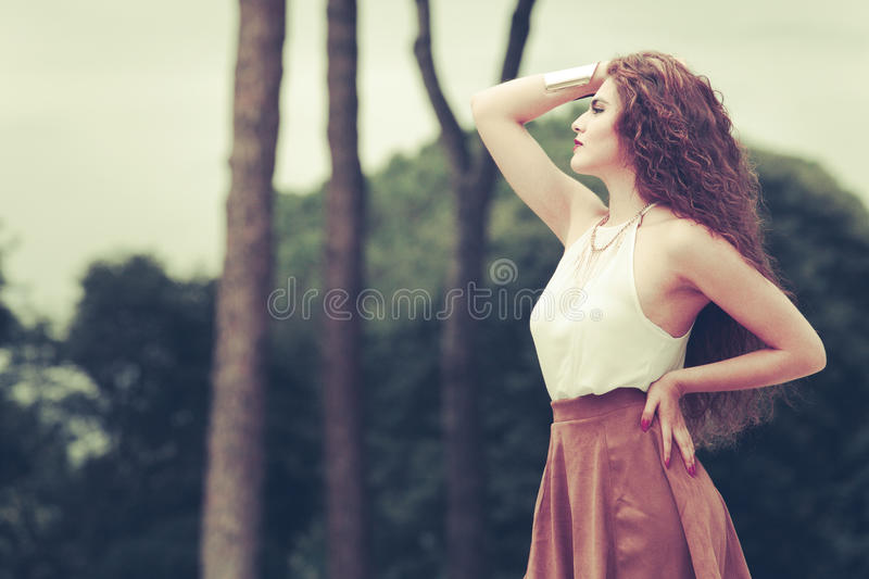 Charming and beautiful young woman with curly hair outdoors stock photos
