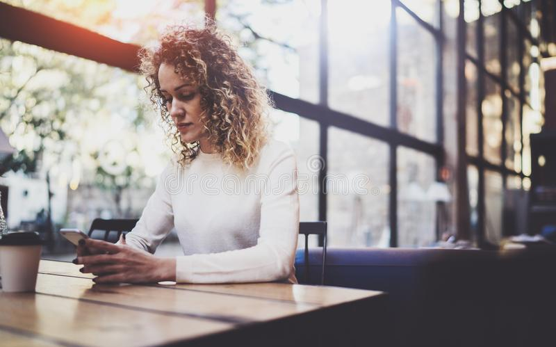 Charming beautiful young woman reading email message on mobile phone during rest time in coffee shop. Bokeh and flares stock images