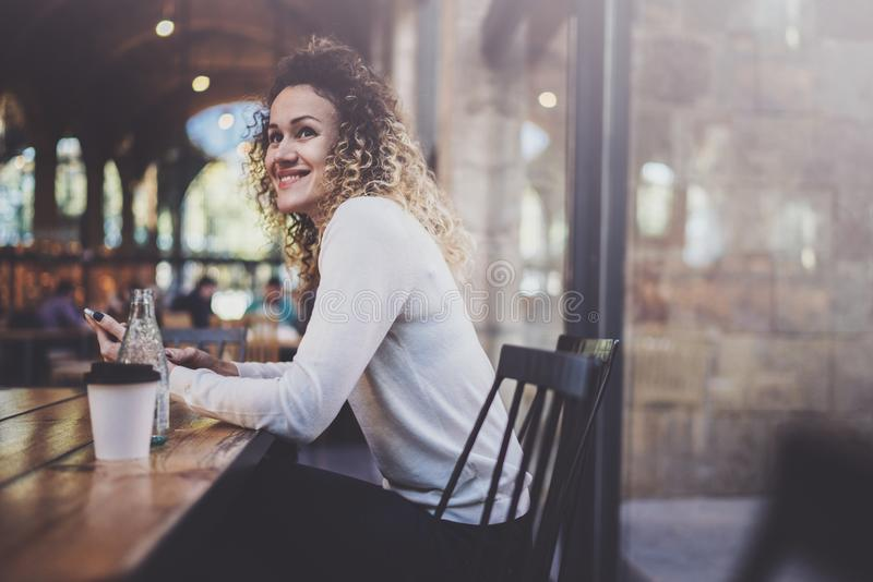 Charming beautiful young woman reading email message on mobile phone during rest time in coffee shop. Bokeh and flares royalty free stock image