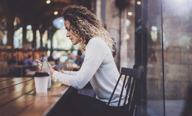 Charming beautiful young woman reading email message on mobile phone during rest time in coffee shop. Bokeh and flares stock photography