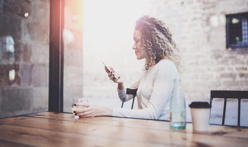 Charming beautiful young woman reading email message on mobile phone during rest time in coffee shop. Bokeh and flares stock photo