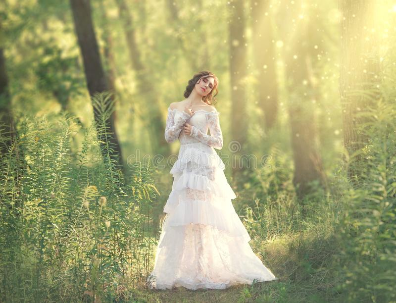 Charming beauty with dark hair standing in light forest, goddess and fairy of morning sun in warm rays, sweet girl in. Long white vintage dress with laces royalty free stock photo