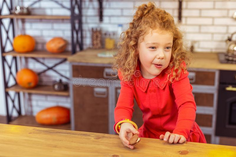 Charming blonde curly-haired girl leaning on table. Express positivity. Cute little female keeping smile on face while looking forward royalty free stock photo