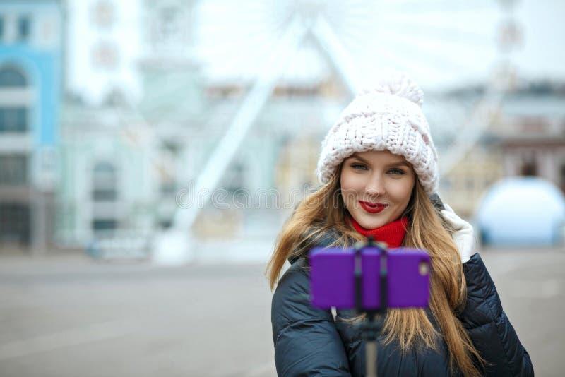 Charming blonde girl tourist wearing knitted cap, taking selfie stock photos