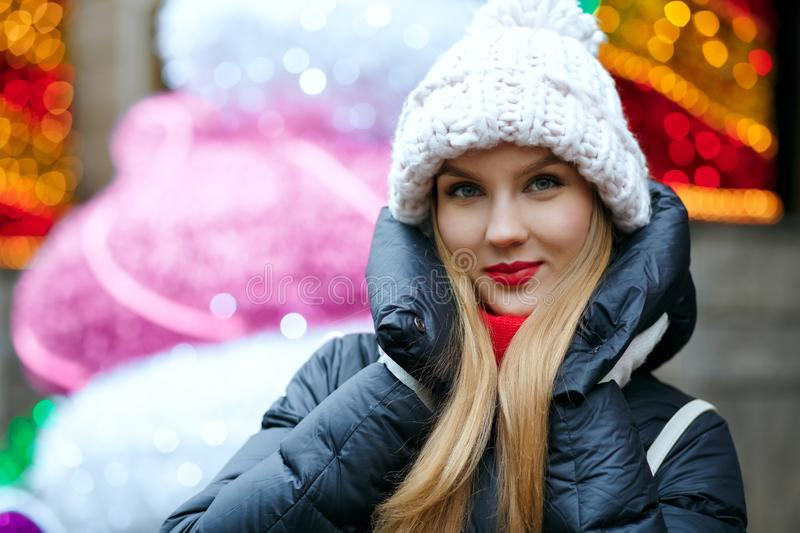 Charming blonde girl wearing knitted cap posing at the street over a garlands background with bokeh royalty free stock photography