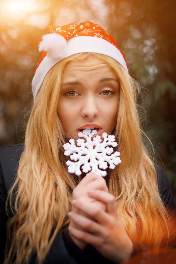 Charming blonde girl wearing santa's hat biting a stock photography