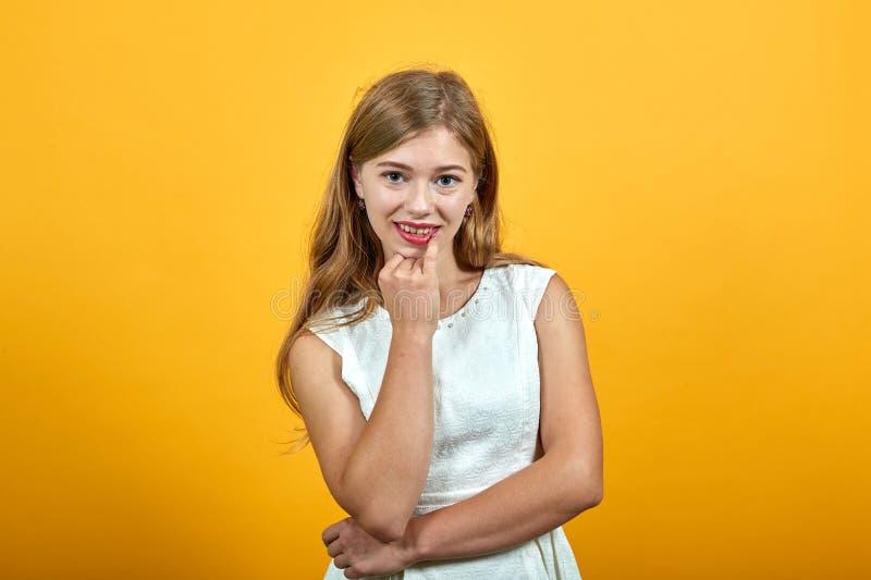Charming blonde jonge caucasiaanse vrouw die hand op kin houdt, lachen stock foto