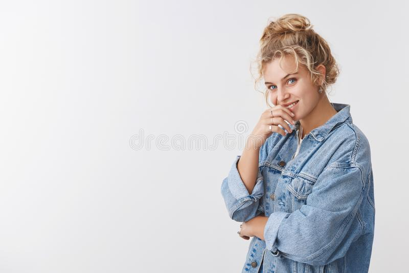 Charming blonde scandinavian curly-haired girl hair combed bun smiling flirty gaze camera coquettish giggling biting royalty free stock images