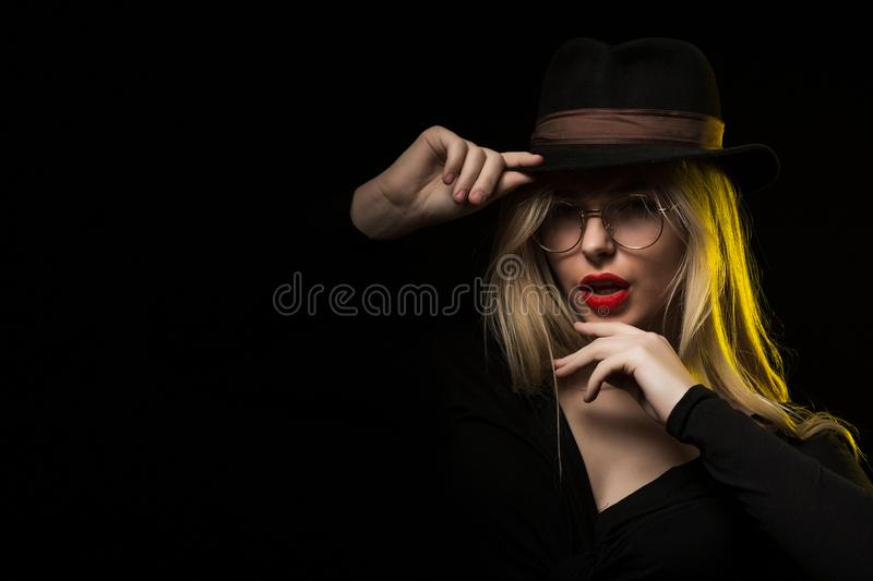 Charming young woman wearing black blouse, hat and glasses, posing in the shadow royalty free stock photography