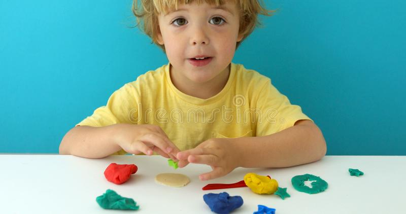 Charming boy with play dough at table stock photography