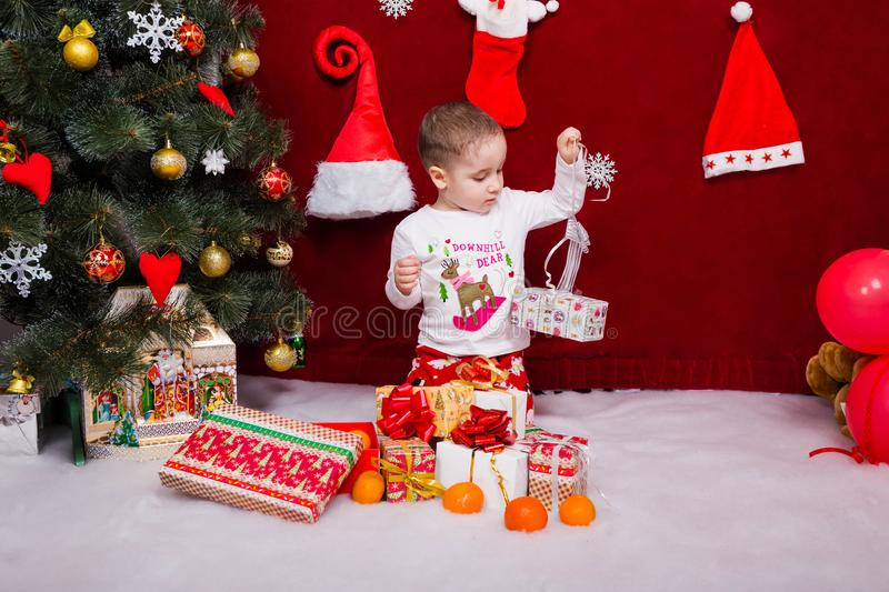 Charming boy unpacks Christmas presents royalty free stock photography
