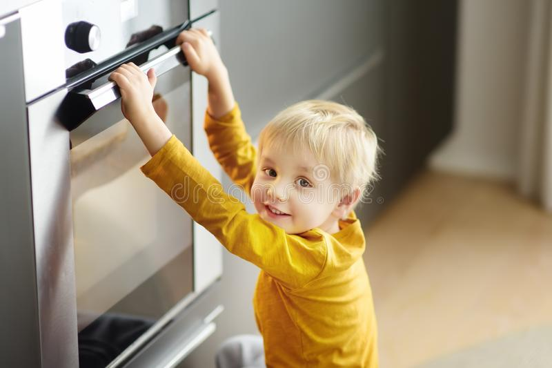 Charming boy waiting preparing food in domestic kitchen. Little mom`s helper looks into oven and waiting cooking apple pie royalty free stock photos