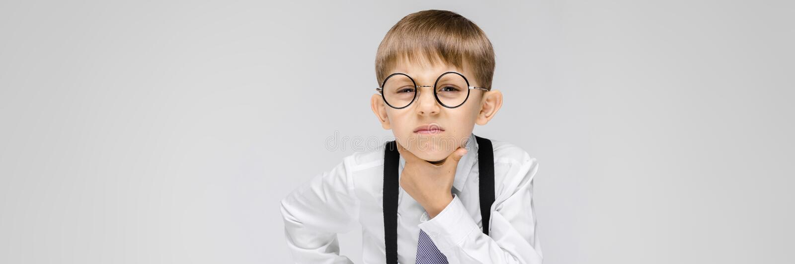 A charming boy in a white shirt, suspenders, a tie and light jeans stands on a gray background. a boy with glasses is. Portrait of a boy on a gray background stock images