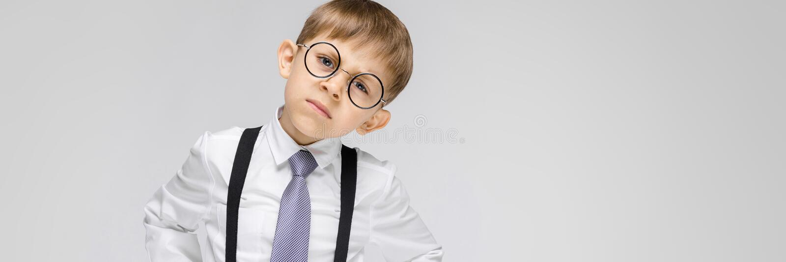 A charming boy in a white shirt, suspenders, a tie and light jeans stands on a gray background. the boy in glasses. Portrait of a boy on a gray background royalty free stock images