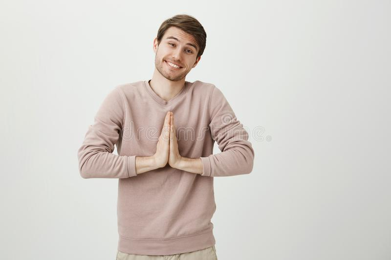 Charming boyfriend with bristle and cute eyes, smiling broadly while standing with praying or begging gesture and asking stock photo