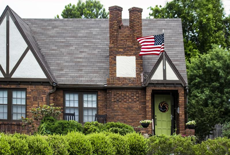 Charming brick house with landscaping and lime green door with wreath and American flag flying with lush trees behind stock photography