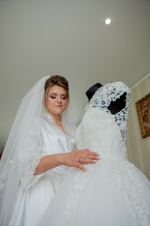 The charming bride with bridesmaids stands near wedding dress. Bridal wedding morning preparation stock photos