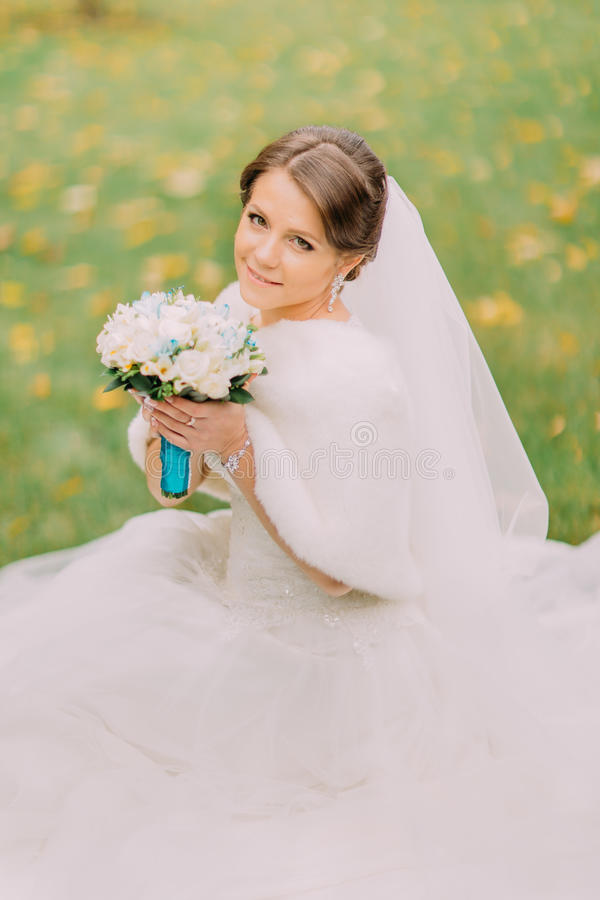 Charming bride in gorgeous white dress with long veil sitting on grass holding wedding bouquet stock photography