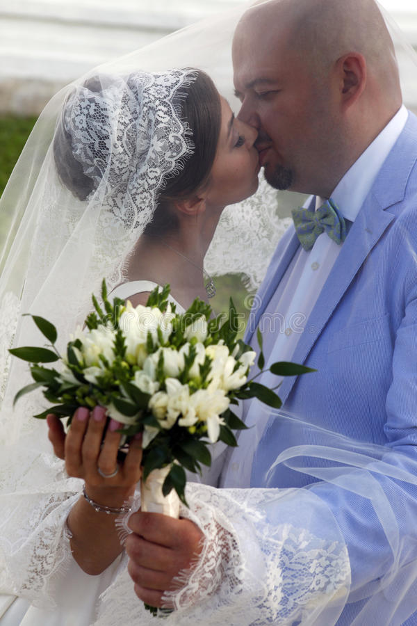 Charming bride and groom. The groom and the bride kiss having closed by a veil royalty free stock photos
