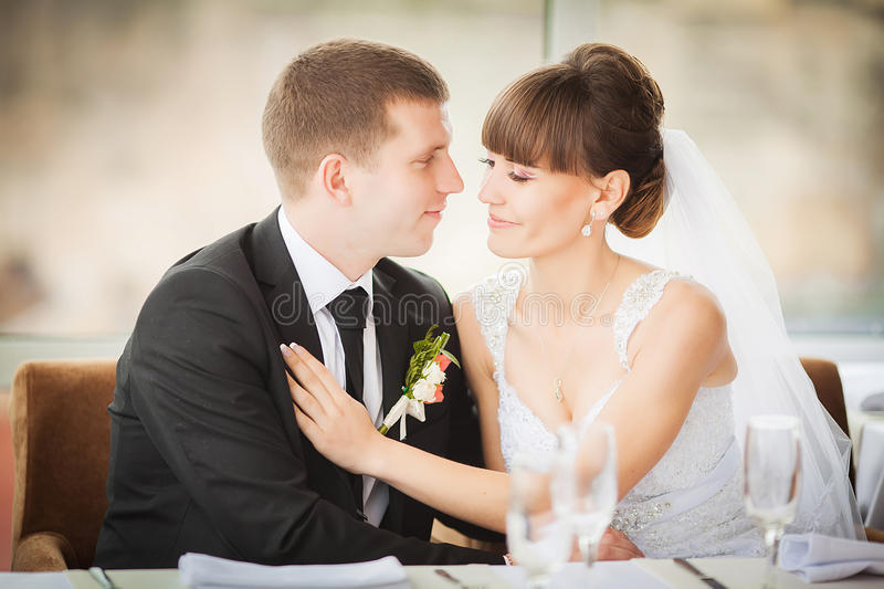 Charming bride and groom on their wedding celebration in a luxurious restaurant. Charming bride and groom on their wedding celebration in a luxurious restaurant stock image