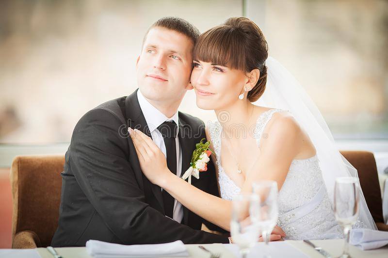 Charming bride and groom on their wedding celebration in a luxurious restaurant. stock photo