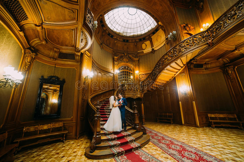 Charming bride and handsome elegant groom holding each other on a background of luxurious vintage interior royalty free stock photos