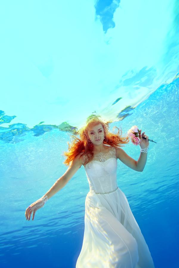 A charming bride with red hair swims and poses for the camera underwater in the pool in a white dress with flowers in her hand on stock photography