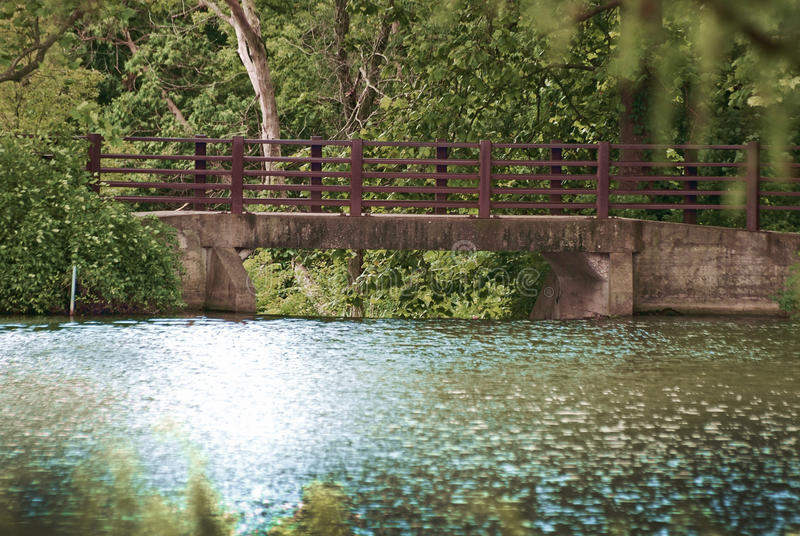 A charming bridge over Lake Marmo at the Morton Arboretum in Lisle, Illinois. A brown painted bridge with stone and brick on a sunny summer day over the stock photos