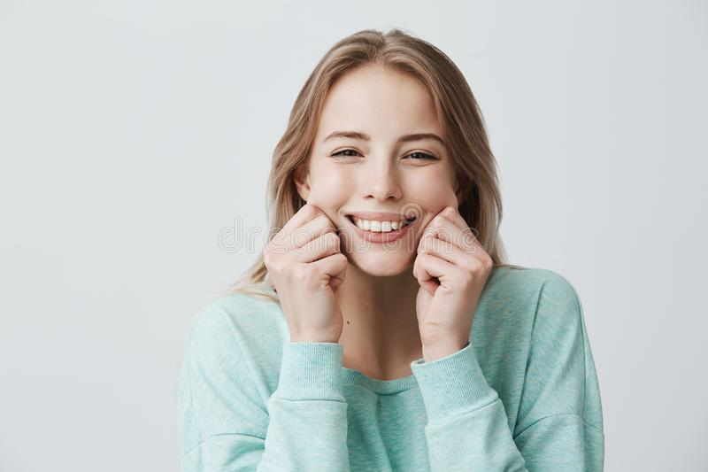 Charming broadly smiling with perfect teeth young European woman with blonde long hair wearing light blue sweater royalty free stock images