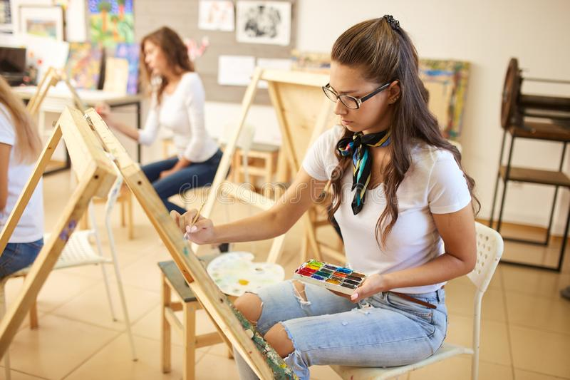 Charming brown-haired girl in glasses dressed in white t-shirt and jeans with a scarf around her neck paints a picture stock image