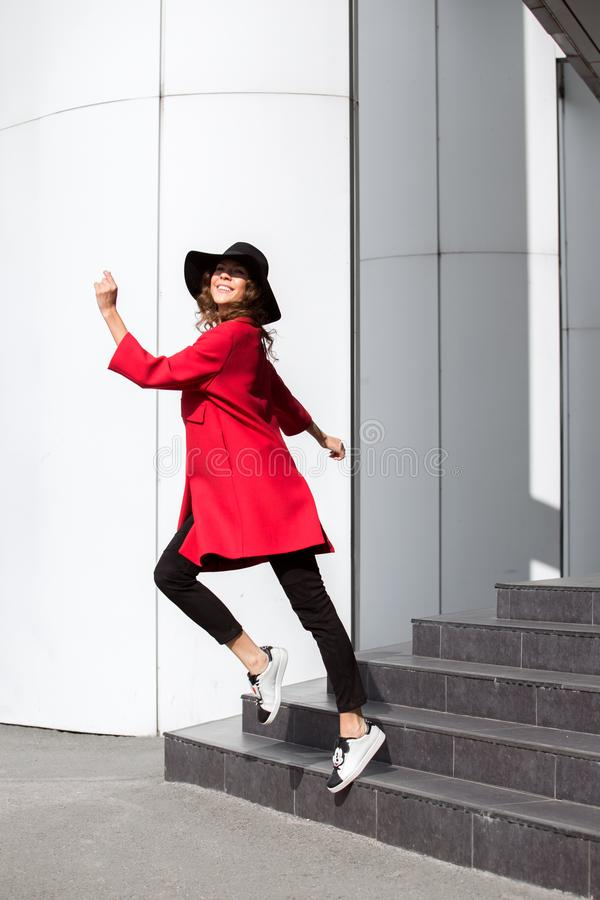 Charming brunette girl dressed in bright red coat and fashionable hat with wide brim poses in the street stock photos