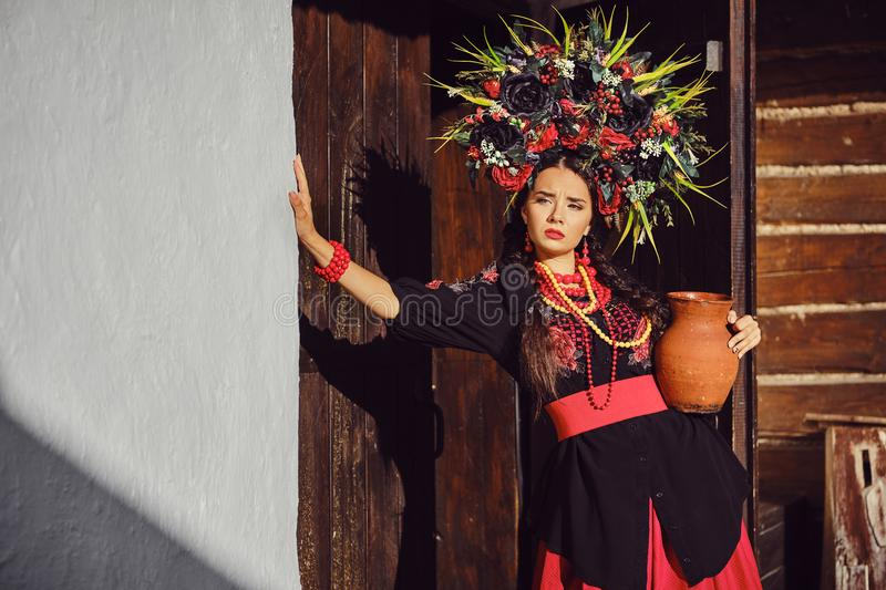 Brunette girl in a white ukrainian authentic national costume and a wreath of flowers is posing standing at the gate. stock photography