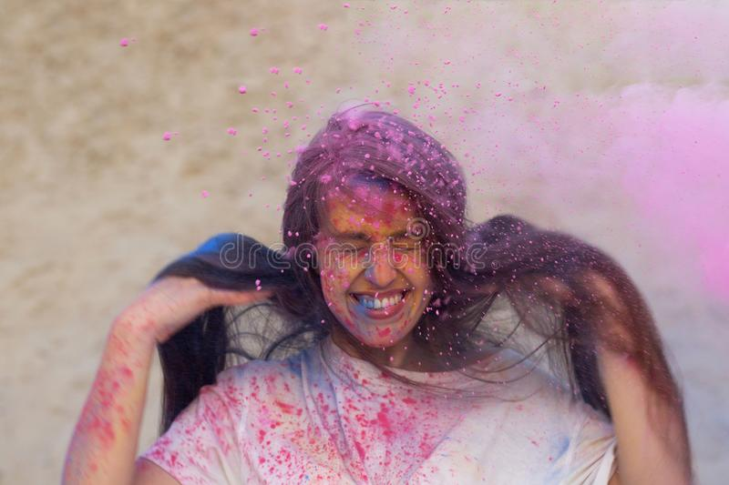 Charming brunette woman with long hair playing with pink dry Holi powder at the desert. Charming brunette model with long hair playing with pink dry Holi powder royalty free stock photo