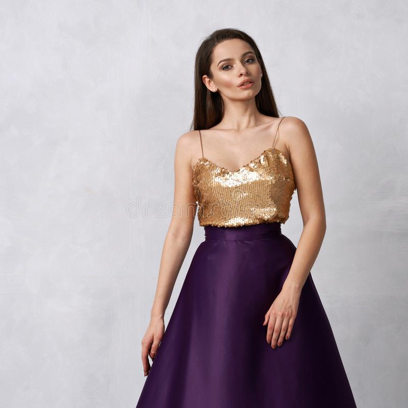 Young woman in formal dress with golden sequin top and purple sa royalty free stock photos