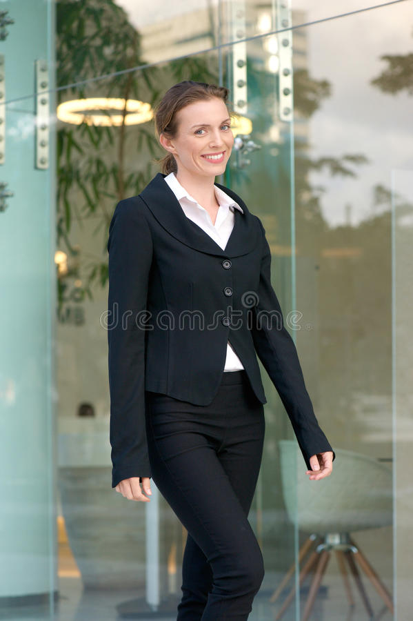 Charming business woman walking outside in the city stock photography