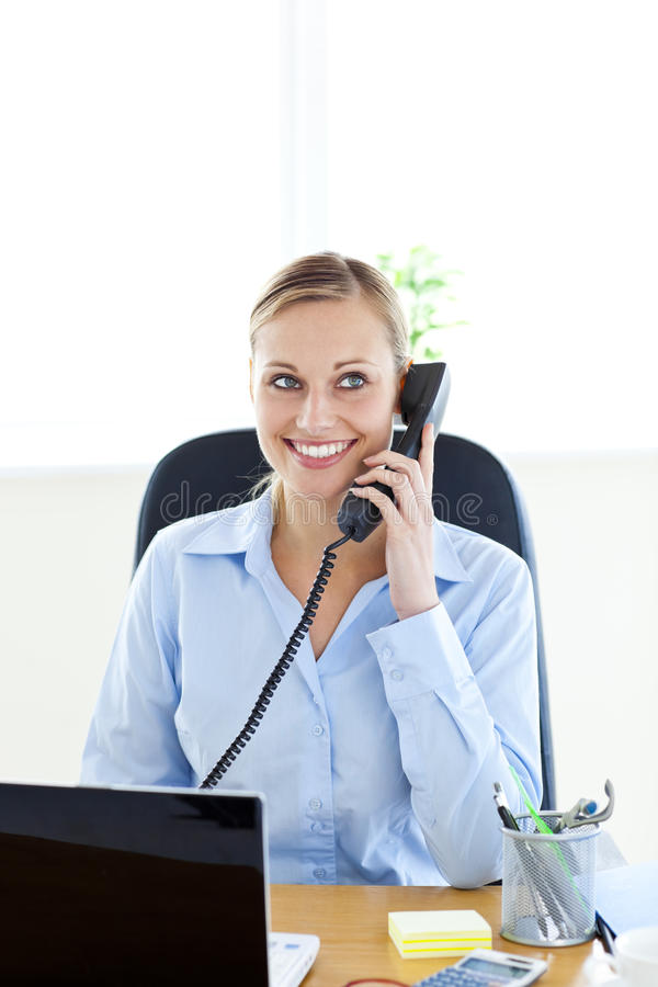Charming businesswoman talking on phone sitting stock photos