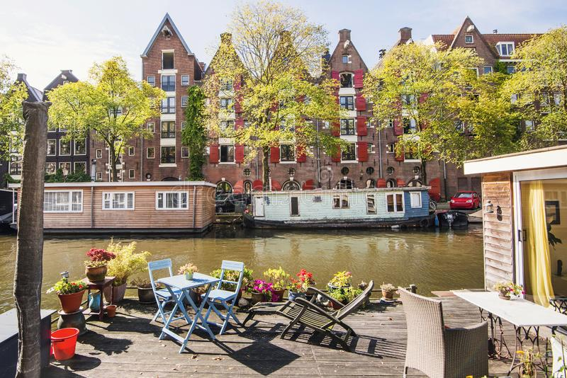 Charming canal with boat houses in Amsterdam old town, Netherlands. Popular travel destination and tourist attraction. Beautiful canal with boat houses in royalty free stock images