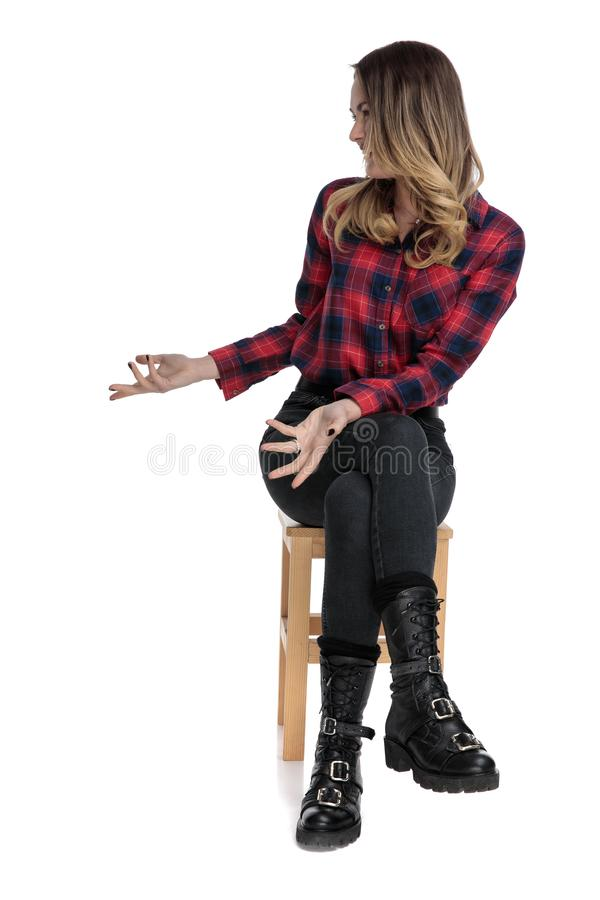 Charming casual woman in checkered shirt sitting and raising hands stock photography