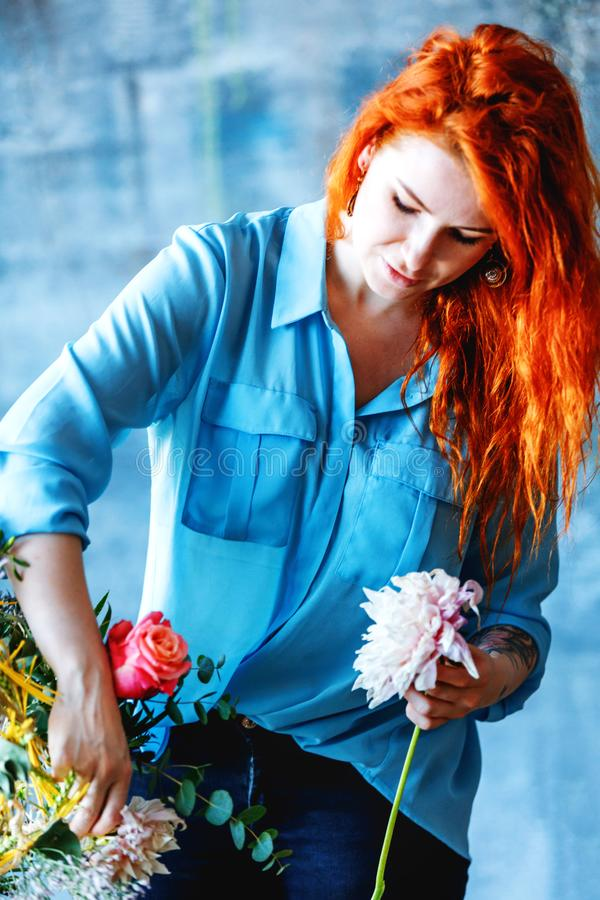 Charming cheerful female shop assistant making bouquet with purple crocus royalty free stock photos