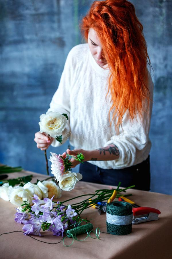 Charming cheerful female shop assistant making bouquet with purple crocus royalty free stock images