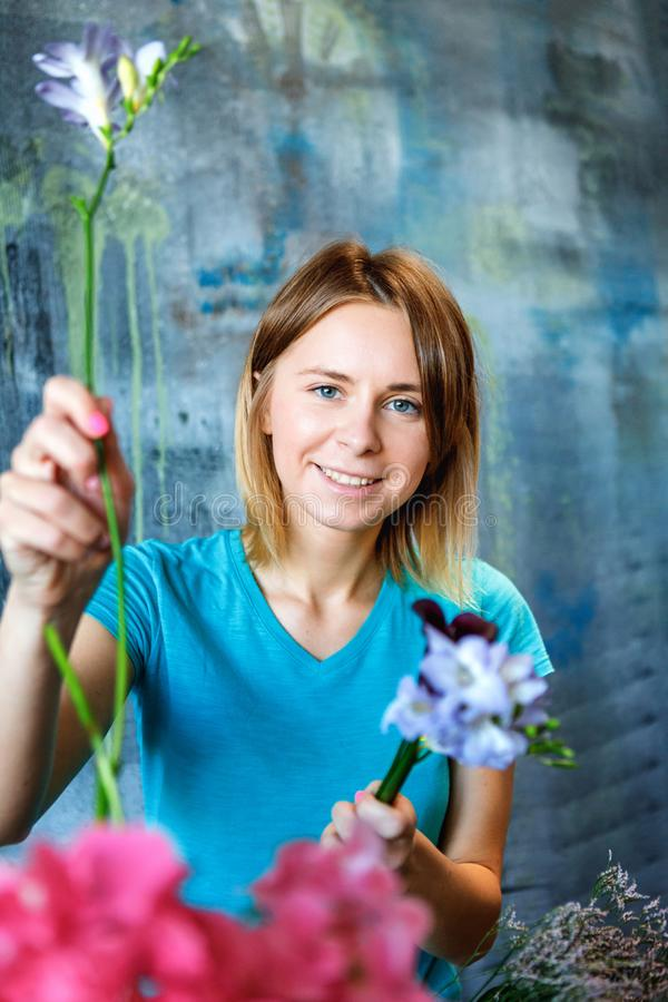 Charming cheerful female shop assistant making colorful pink bouquet with Hydrangea purple, phlox and calla stock photography