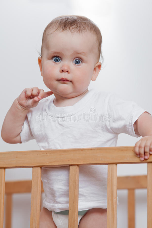 Charming child in the crib. Charming baby in white looking at camera royalty free stock images