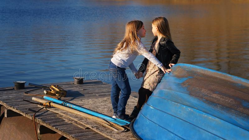 Little sisters on the pier. Charming children schoolgirls spending time by lake. Two kids playing on wooden pier. Fall weekend in open air. Leisure activity royalty free stock photography